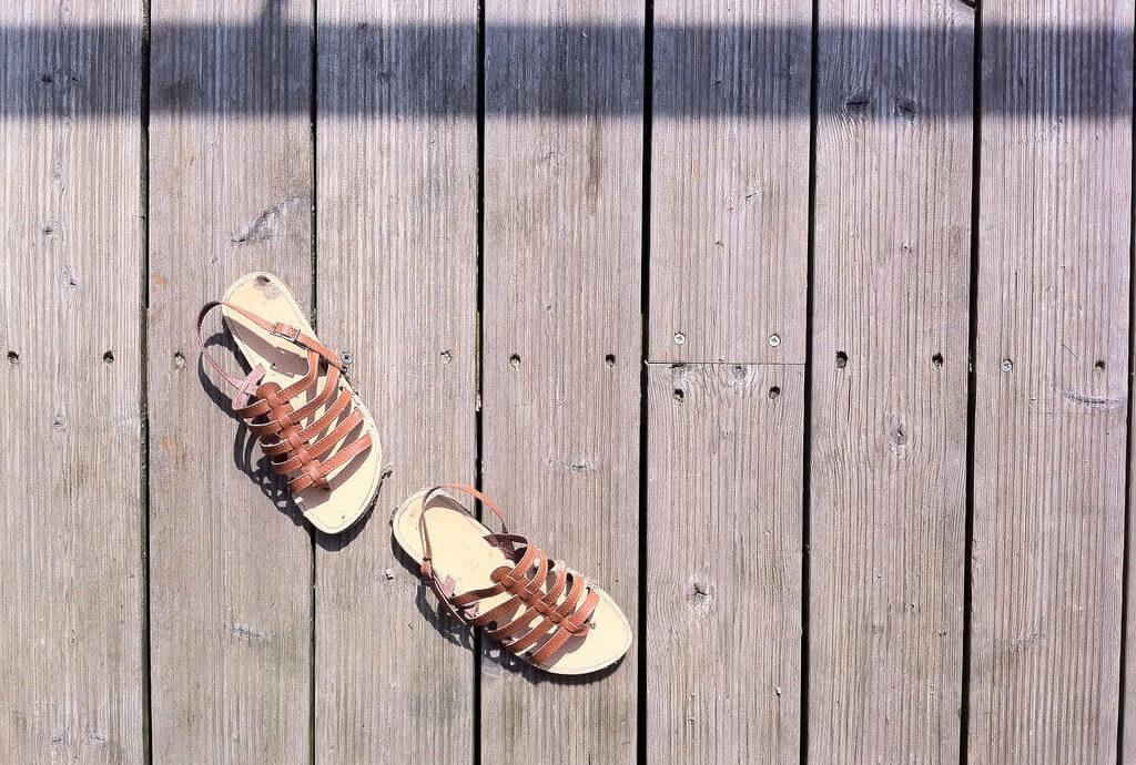 sandales tropéziennes marron sur terrasse en bois